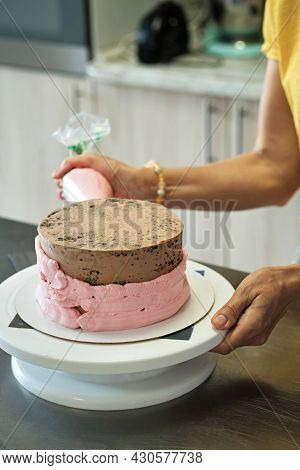 Woman Making Chocolate Cake With Pink Cream, Close-up. Cake Making Process, Selective Focus