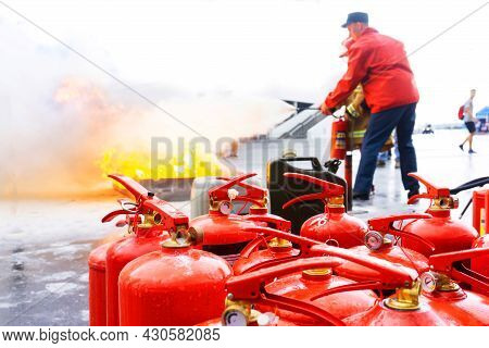 Many Fire Extinguishers In A Fire Safety Lesson. The Process Of Extinguishing Open Fire