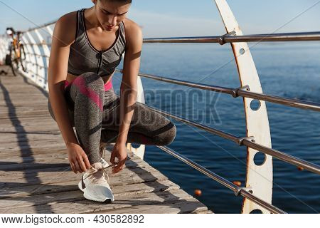 Cropped Shot Of Fitness Woman Tying Her Shoelaces On The Seaside Promenade, Workout And Jogging On P