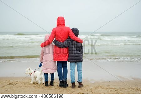 Family Of Three Having Fun With Their Dog At Winter Beach On Cold Winter Day. Kids Playing By The Oc