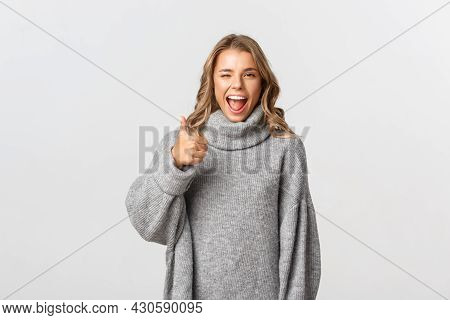 Portrait Of Attractive Happy Woman In Grey Sweater, Encourage You, Showing Thumb-up In Approval And