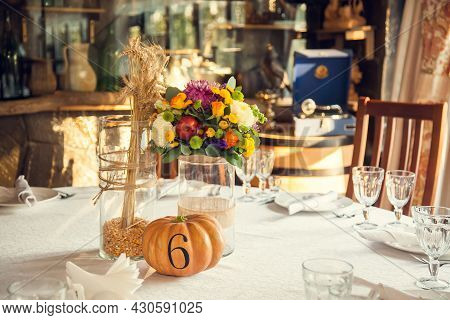 Festive Floristry In Autumn Style With Numbering Of Tables On Pumpkins In Banquet Hall. Floristry An