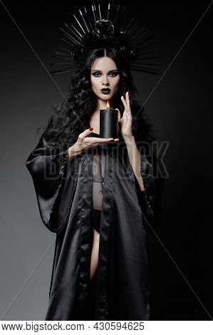 Halloween Theme: Dangerous Young Witch Dressed In Black Cloak And Headwear With Roses And Spikes. Da
