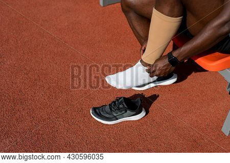 A Black Male Track And Field Athlete Puts Compression Leggings On His Leg Before A Race At The Stadi