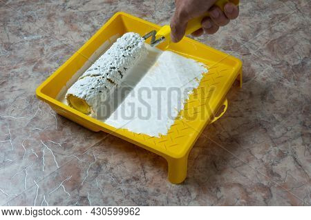 A Man's Hand Drives A Roller Along The Pallet Of Paint. White Paint In A Yellow Pallet.