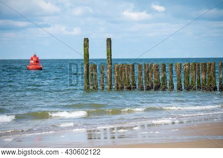 View On Wooden Poles At White Sandy Beach North Sea Beach Near Zoutelande, Zeeland, Netherlands