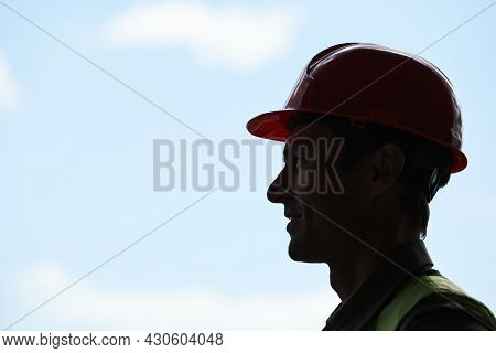 Backlit Side View Portrait Of Male Construction Worker Wearing Hardhat While Standing Against Sky In