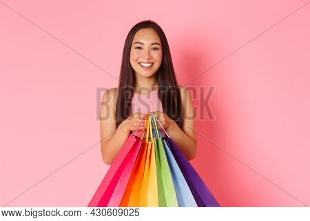 Close-up Of Beautiful And Trendy Asian Girl Shopaholic, Holding Shopping Bags And Pointing At Hersel