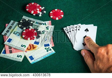 Player Points With His Finger At A Winning Flush Combination In Poker Game On A Table With Chips And