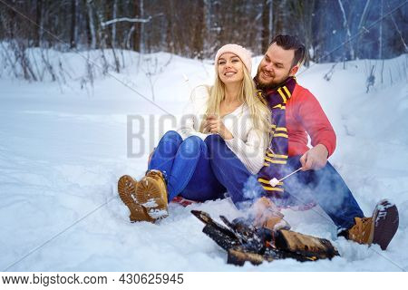 Happy Couple Man And Woman In Winter In The Forest Fry Marshmallows On The Fire, Romantic Picnic