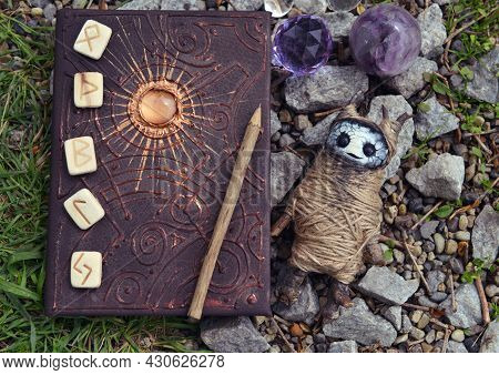 Witch Book Of Magic Spells, Runes, Voodoo Doll And Crystals In The Garden.  Esoteric, Gothic And Occ