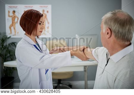 Serious Physiotherapist Asking Senior Patient To Stretch Out Arm When She Is Checking His Injury