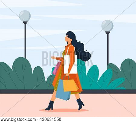 After Shopping Concept. Beautiful Woman With Colorful Bags Of Clothes Walking Down Street From Fashi