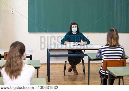 Teacher and her students wearing protective face mask in the classroom. Social distance and classroom safety during coronavirus epidemic