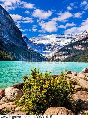 Glacial Lake Louise. Sunny fine day. Travel to the Rocky Mountains of Canada. The lake with azure water is surrounded by mountains and forests. The concept of ecological, active and photo tourism