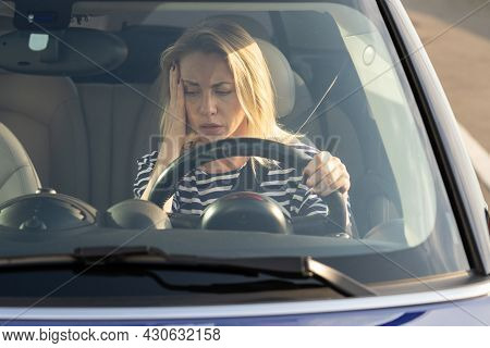 Upset Woman Of Middle Age Looking At Car Dashboard. Anxious Female Driver In Broken Car Out Of Fuel