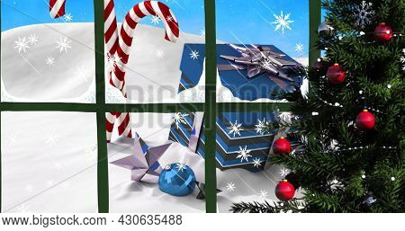 Digital image of window frame and christmas tree against snow falling over christmas candy canes, gift box and bauble decoration on winter landscape. christmas festivity celebration tradition