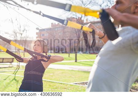 Fitness Couple Exercising With Fitness Straps In The Park