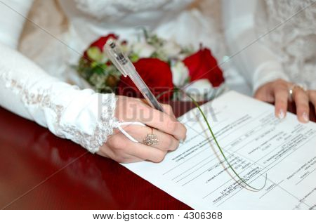 Bride With Wedding Bouquet Signing Marriage Lines.