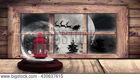 Image of snow globe with lantern and silhouette of santa claus in sleigh being pulled by reindeer and winter christmas scenery with full moon seen through window. christmas festivity celebration