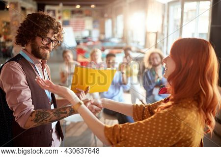 young redhead female congratulate to a caucasian business student after successful attending seminar, giving him certificate in folder. selective focus image.