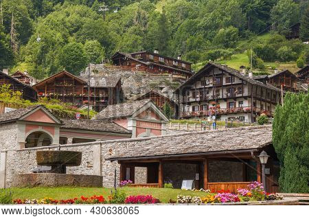 Alagna Valsesia, Italy - July 20, 2021: Panoramic View Of Small Alpine Town With Flowers In The Summ