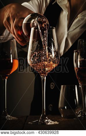 Sommelier Pouring Rose Wine Into Glass At Wine Tasting In Winery, Bar Or Restaurant. Toned Image