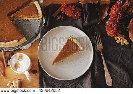 Pumpkin Pie Slice On Modern Plate And Hot Coffee On Rustic Table With Linen Napkin, Autumn Flowers A