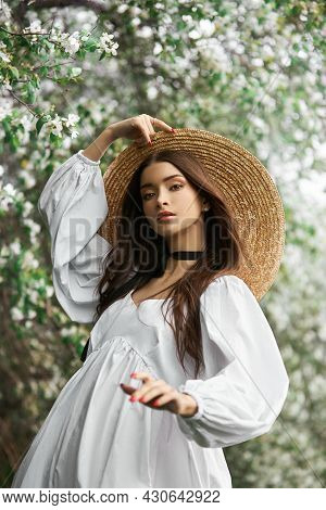 Brown-haired Woman In A Large Straw Hat And A White Dress Poses Against The Background Of Blooming W