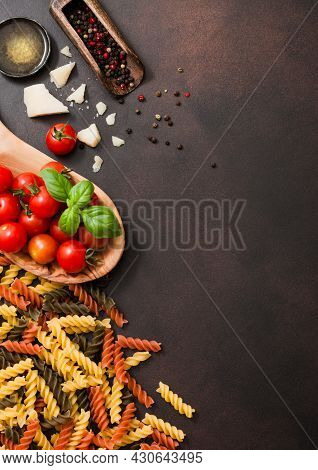 Fresh Raw Fusilli Pasta With Tomatoes In Wooden Bowl With Oil And Parmesan Cheese With Salt On Dark