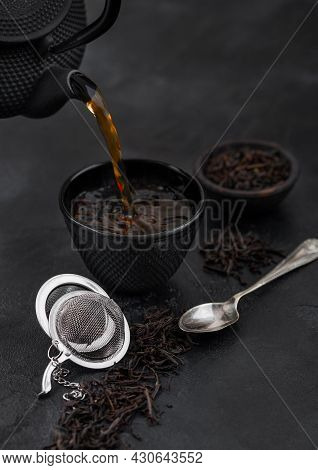 Pouring Black Tea From Teapot To Cup With Strainer Infuser And Loose Tea On Black With Silver Spoon.