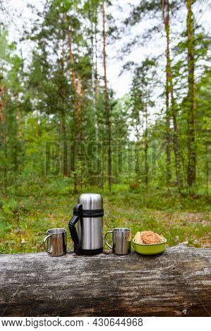 Picnic In The Pine Forest. A Thermos And Metal Mugs Stand On An Old Log Against The Backdrop Of A Fo