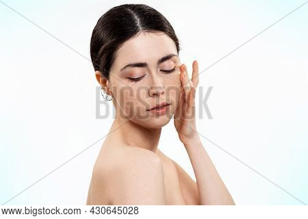 Beauty And Skin Care. Portrait Of A Young Beautiful Caucasian Woman Touching Her Skin. White Backgro