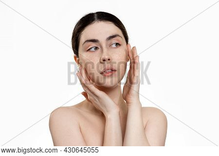 Beauty And Skin Care. Portrait Of A Young Beautiful Caucasian Woman Looking At Her Face. White Backg