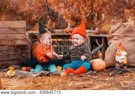Halloween And Autumn Holidays. Funny Boy In A Dwarf Costume And A Girl In A Witch Costume, Surrounde