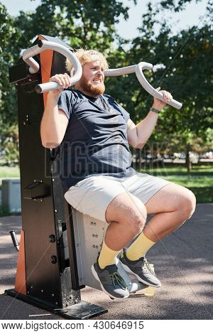 Overweight Man Exercising On Sports Equipment He Lifting Weights And Building His Muscular Outdoors
