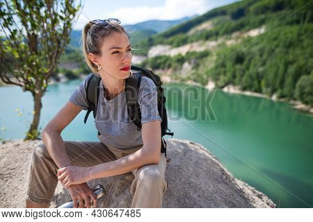 Mid Adult Woman Tourist On Hiking Trip On Summer Holiday, Resting By Lake.