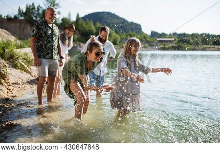 Happy Multigeneration Family On Walk By Lake On Summer Holiday, Having Fun In Water.