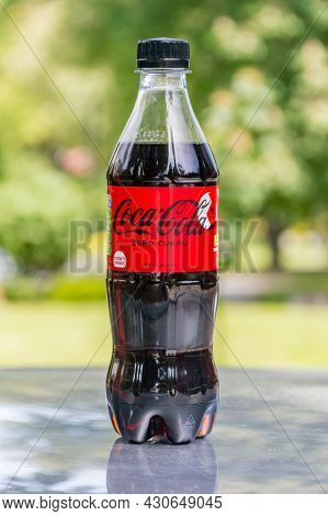 Gliwice, Poland - June 4, 2021: Bottle Of Sugar Free Coca-cola With Blurred Tree In Background.