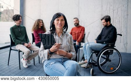 Counselor With Men And Women Sitting In Circle During Group Therapy, Looking At Camera.