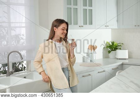 Woman Drinking Tap Water From Glass In Kitchen