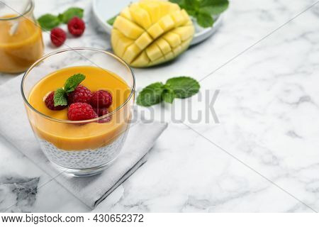 Delicious Chia Pudding With Mango Sauce And Raspberries On White Marble Table. Space For Text