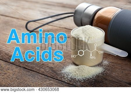 Measuring Scoop Of Amino Acids Powder On Wooden Table