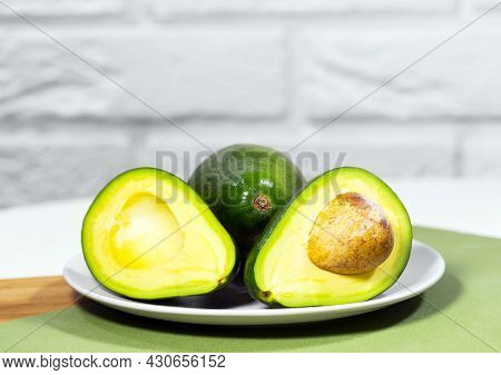 Halves Of Ripe Avocado On Bowl Served On Table, Green And White Background, Healthy Oily Food, Keto