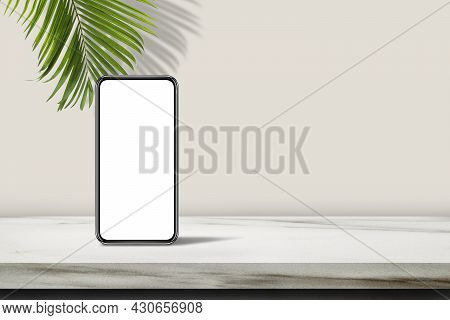 Smartphone With White Blank Screen On Marble Table Top With Green Palm Leaves In Background.