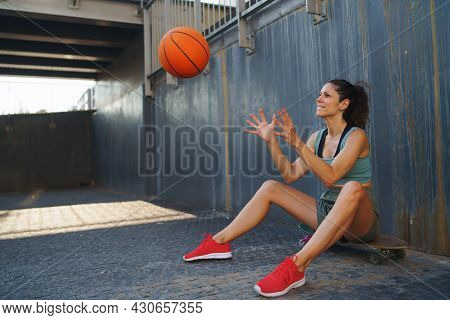 Mid Adult Woman With Basketball Outdoors In City, Sitting And Resting.