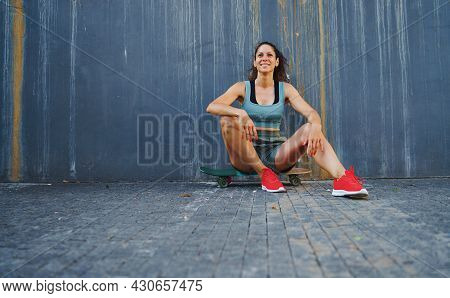 Front View Portrait Of Mid Adult Woman Sitting On Skateboard Outdoors In City, Resting.