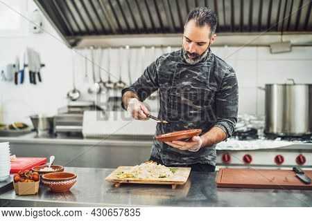 Professional Cook Is Serving Meal In Restaurant's Kitchen.