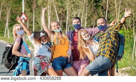 Happy Mixed Race Group Of Best Friends Wearing Face Mask Embracing And Having Fun On Trip Adventure