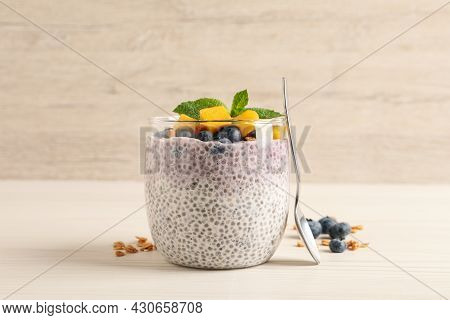 Delicious Chia Pudding With Blueberries, Mango And Mint On White Wooden Table